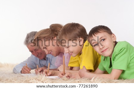 lying family on a carpet on a white