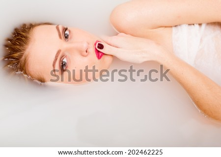 lying in the spa milk water bath beautiful tender young blond woman having fun posing sensually touching her red lips with finger & looking at camera on light copy space background closeup portrait - stock photo