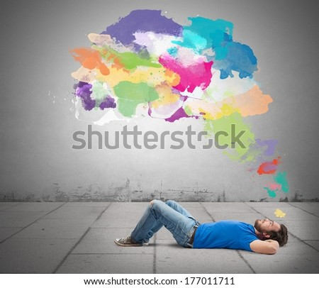 Lying man thinking creatively with colorful splash - stock photo