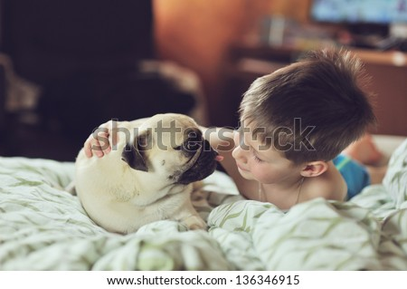 lying on a soft bed with her boy friend breed pug puppy - stock photo