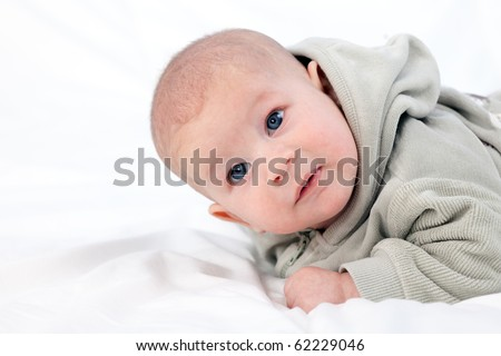 lying on duvet two months old baby boy in grey sweatshirt