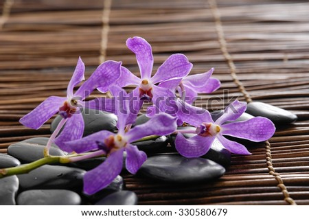 Lying on purple orchid with stones on bamboo mat  - stock photo