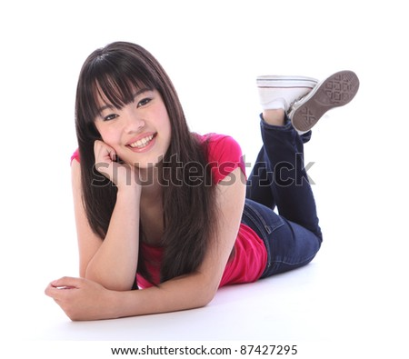 Lying on the floor a beautiful young Japanese teenager high school student girl, with long black hair wearing blue denim jeans and a pink t shirt with big happy smile. - stock photo