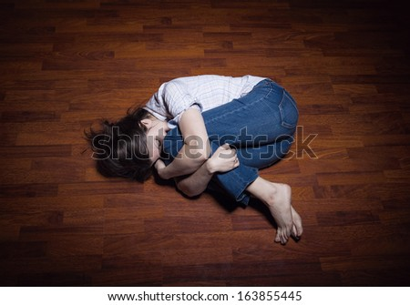 Lying on the floor of a lonely young woman in a empty room