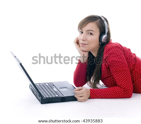 Lying on the floor young girl working on laptop and listening music from mp3 player. - stock photo
