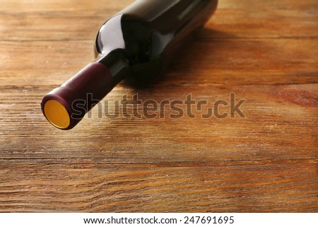 Lying red wine bottle on wooden table - stock photo