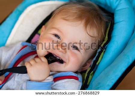 lying small baby, smiling baby, baby has something in mouth, hold with teeth, lying in deck chair for baby - stock photo
