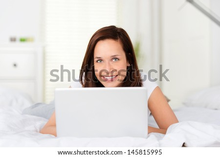 Lying woman browsing using her laptop on bed - stock photo
