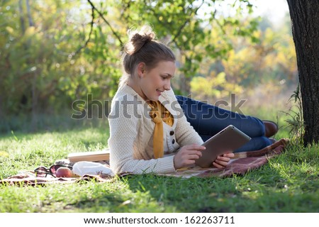 Lying woman on mat using tablet computer - stock photo