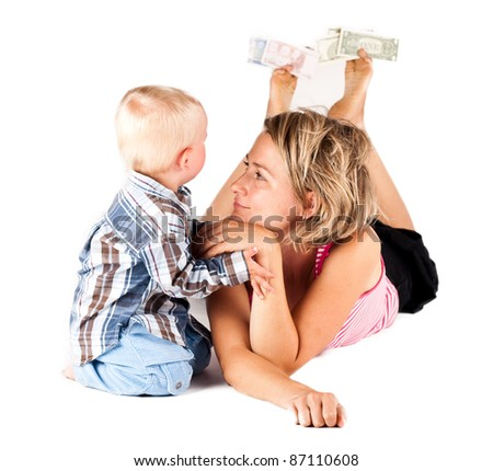 lying woman playing with a child, between the toes holding money - stock photo