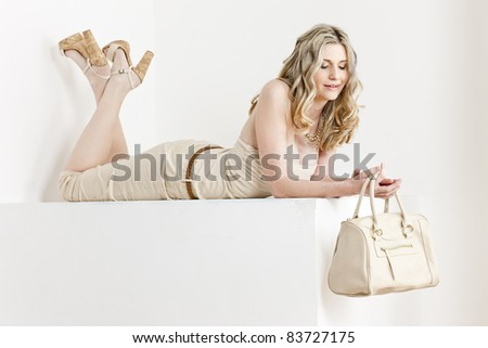lying woman wearing summer clothes and shoes with a handbag - stock photo