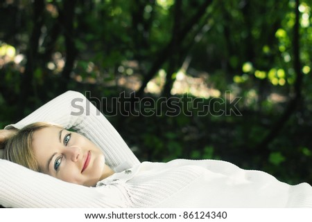 Lying young blue-eyed smiling woman in white against blurred forest background with selective focus and copy space - stock photo