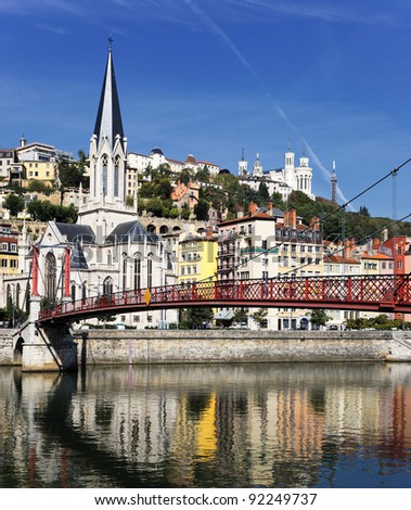 Lyon city with red footbridge on Saone river and church - stock photo