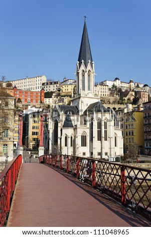 Lyon with famous red footbridge on Saone river and church - stock photo