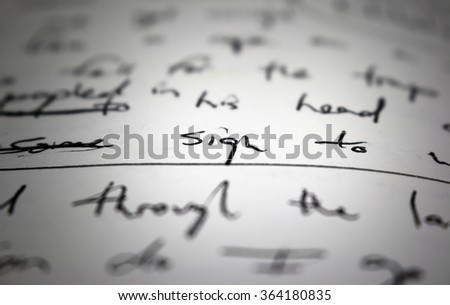 "Lyrics written in ink on paper, closeup/focus on the word ""sign"""