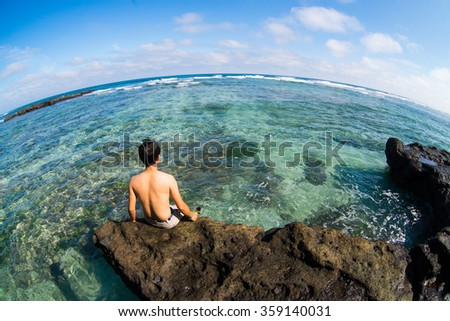 LYSON, VIETNAM - JANUARY 4, 2016: Young man sit on rock near the beautiful beach in Ly Son island in Quang Ngai, Vietnam.