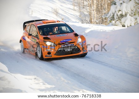 LYSVIK, SWEDEN - FEB 11: Henning Solberg driving his Ford Fiesta WRC during the World Rally Championship event Rally Sweden in Lysvik, Sweden on Feb 11, 2011 - stock photo