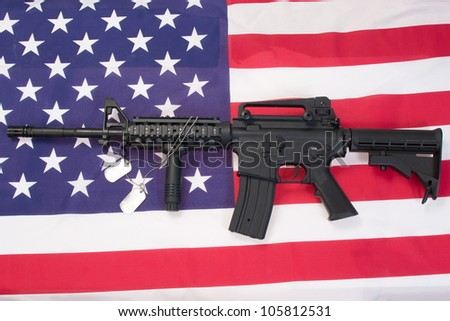 M4A1 assault rifle with blank dog tags on us flag - stock photo