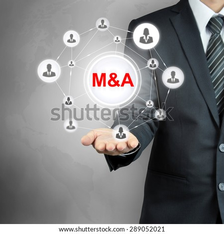 M & A (Merger & Acquisition) sign connected with businesspeople icon network on businessman hands - stock photo