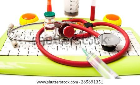 M?edicine, phonendoscope, bottle, the keyboard, ball pens syringe, needle, injection on a white background - stock photo