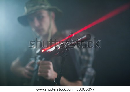 M16 laser rifle being held by young soldier.