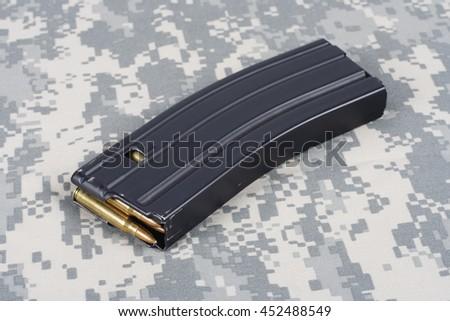 M-16 magazine with cartridges on camouflage uniform background - stock photo