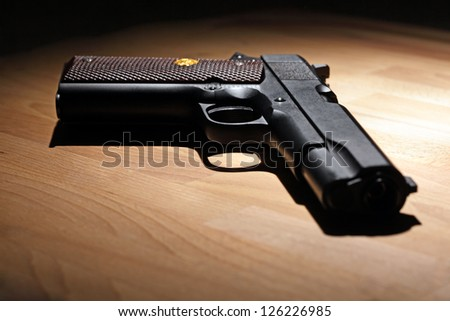 M1911 pistol on the wooden table. Shallow DOF. - stock photo
