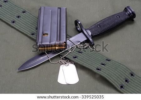 M16 rifle bayonet on uniform bacground - stock photo