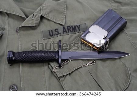 M16 rifle bayonet on uniform background - stock photo