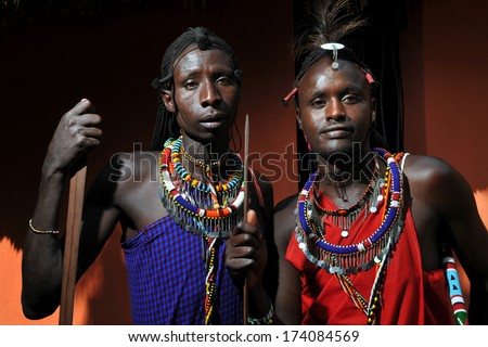 MAASAI MARA, KENYA - AUGUST 10: Maasai men in traditional clothing on August 10, 2010. The Maasai are the most famous tribe in Africa. They are nomadic and live in small villages.. - stock photo