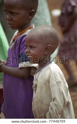 MAASAI MARA, KENYA - FEBRUARY 4: An unidentified around 5 years old Maasai boy, 4 February , 2004 at Masaai Mara, Kenya. The Maasai are the most famous tribe in Africa. They are nomadic and live in small villages. - stock photo