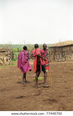 MAASAI MARA, KENYA - FEBRUARY 4: Maasai morani in the village, 4 February , 2004 at Masaai Mara, Kenya. The Maasai are the most famous tribe in Africa. They are nomadic and live in small villages. - stock photo