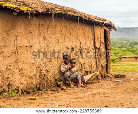 MAASAI MARA, KENYA - OCTOBER 17, 2014 : Two african boys sitting in front of a Masai tribe village house - stock photo