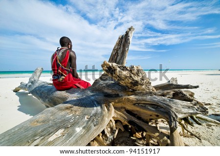 Maasai sitting by the ocean on the beach - stock photo
