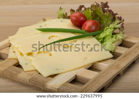 Maasdam cheese slices on the wooden background