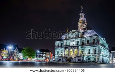 MAASTRICHT, NETHERLANDS, APRIL 12, 2014: Night view over markt which is one of the historical centers of maastricht with majestic town hall and wide square full of restaurants.
