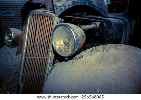 MAASTRICHT, NETHERLANDS - JANUARY 09, 2015: Fragment of a rusty body of a compact car Renault Monaquatre, 1934. Vintage toning. Stylization. International Exhibition InterClassics & Topmobiel 2015 - stock photo