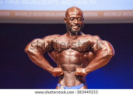 MAASTRICHT, THE NETHERLANDS - OCTOBER 25, 2015: Male bodybuilder Elias Bogane flexes his muscles and shows his best physique in a front lats spread pose on stage at the World Grandprix Bodybuilding