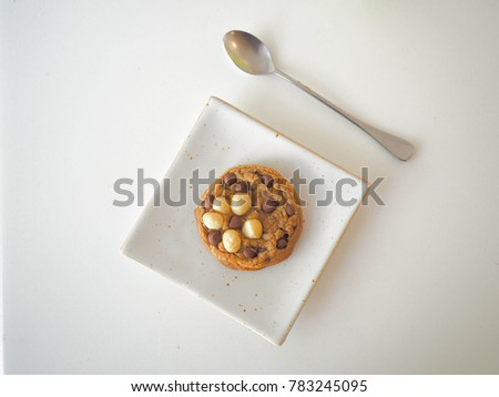 Macadamia and chocolate chips cookie in white plate and spoon on white table