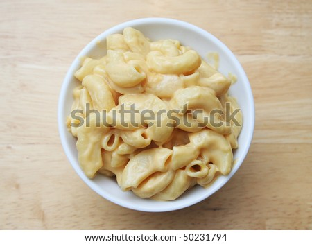 Macaroni and Cheese in a white bowl on a butcher block table - stock photo