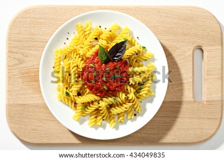 Macaroni fusilli with tomatoes sauce in white ceramic plate on wooden cutting board.  Close up, top view, high resolution product. - stock photo