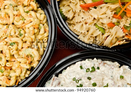 Macaroni salad, pasta salad and potato salad in containers ready to be served. - stock photo