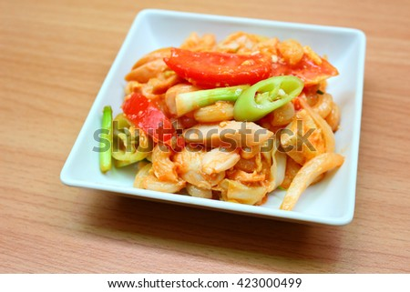 Macaroni Salad with chicken meat, sausage, pepper, tomato. onion and onion leaf on white dish and wooden background.