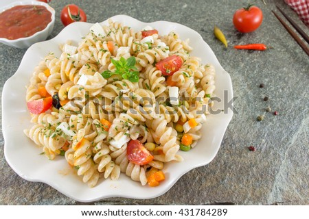 macaroni served with cheese vegetables and parsley. Colorful meal - stock photo