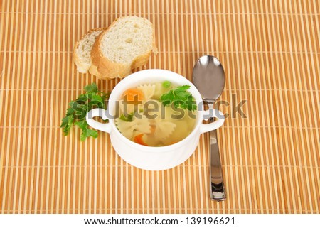 Macaroni soup in a bowl, bread slices, a spoon and parsley on a bamboo cloth - stock photo