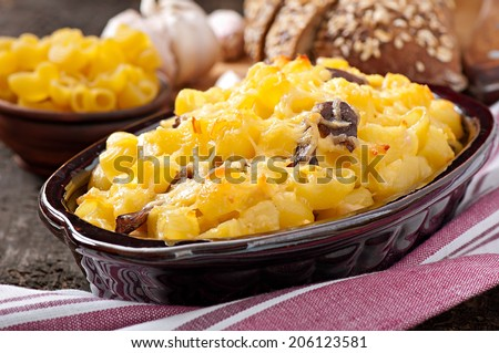 Macaroni with cheese, chicken and mushrooms baked in the oven - stock photo