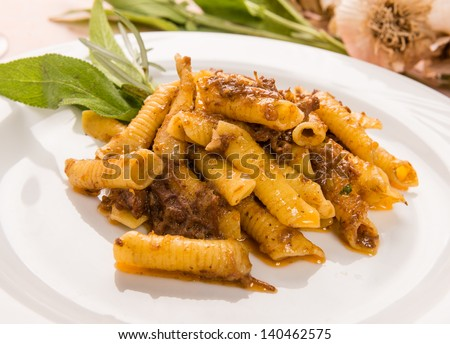 Macaroni with game sauce in white dish, close-up - stock photo