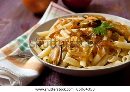 macaroni with mussels and sweet onion on wood background