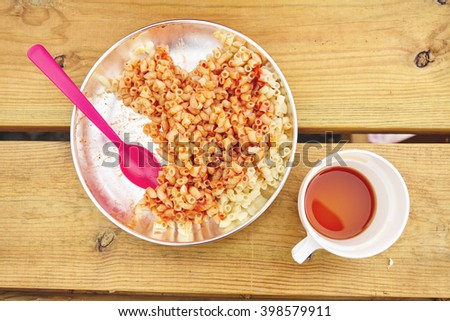 Macaroni with tomato sauce on metal camping plate, tea cup, on wooden picnic table top - stock photo