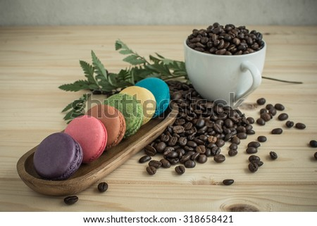 Macarons and cofee bean on wooden table and vintage color tone - stock photo